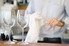 O garçom limpa os vidros de vinho Fotos de Stock