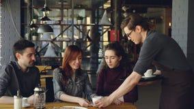 O garçom masculino amigável está trazendo copos de chá aos estudantes alegres que sentam-se na tabela no café Indústria do alimen video estoque
