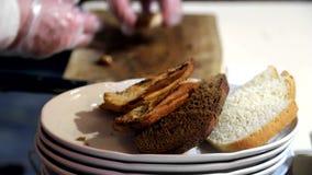 O garçom nas luvas de põe o pão sobre uma placa, e prepara-o para a entrega vídeos de arquivo