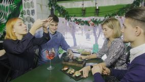 O garçom no avental está servindo o aperitivo aos jovens A mulher toma uma foto do alimento na tabela video estoque