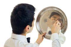 O garçom novo com as ceras do cabelo preto para brilhar a bandeja para o close-up dos armários foto de stock