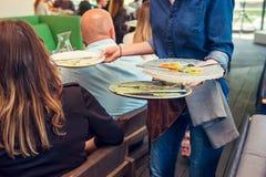 O garçom que remove os pratos sujos após convidados do evento no serviço do restaurante O serviço da restauração na reunião de ne imagens de stock