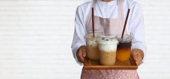 O garçom que veste o avental cor-de-rosa leva 3 leva embora copos do café de gelo para servir no fundo branco do tijolo com espaç fotos de stock