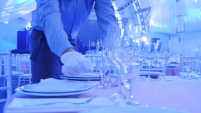 O garçom serve uma tabela no restaurante, usando diversos vidros para o vinho, placas, facas, forquilhas Serviço excelente de video estoque