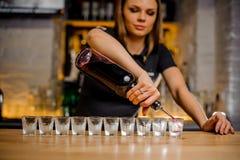 O garçonete derrama o álcool nas pilhas de cristal que são alinhadas imagens de stock royalty free