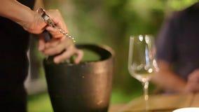 O gar?om abre uma garrafa do vinho na cubeta com gelo no restaurante 1920x1080 video estoque