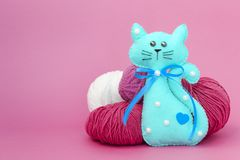 O gato do brinquedo das crian?as fez do feltro em um fundo colorido ao lado das bolas do fio foto de stock royalty free