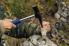 O geólogo examina uma amostra mineralogia com a ajuda de um martelo geological imagens de stock royalty free