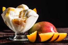 O gelado do molho do caramelo e a manga fresca frutificam fotografia de stock