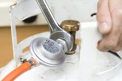 O gerador do gás conecta a mangueira flexível do cilindro de gás ao fogão de gás Fotografia de Stock Royalty Free