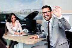 O gerente de vendas em um carro da sala de exposições vale ao comprador imagem de stock