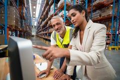 O gerente e o trabalhador estão olhando um computador imagens de stock