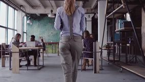 O gerente fêmea moreno vem ao escritório moderno A jovem mulher cumprimenta com colegas, traz o café ao amigo Mo lento filme
