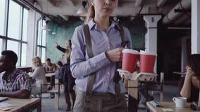 O gerente fêmea moreno vem ao escritório moderno no trabalho A jovem mulher cumprimenta com colegas, traz o café ao amigo filme