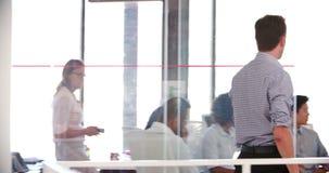 O gerente Leaves Office And junta-se à reunião do pessoal no escritório vídeos de arquivo