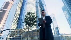O gerente masculino está andando ao longo do complexo do negócio composto dos arranha-céus metragem da câmera do cinema 6K video estoque