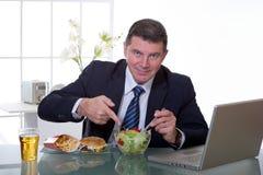 O gerente no escritório come a salada verde imagem de stock