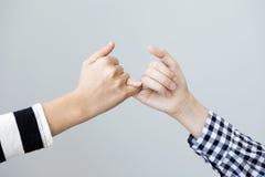 O gesto das mãos significa a promessa no fundo cinzento foto de stock