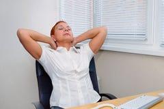 O gestor de escritório da menina amassa os músculos cansados do pescoço inclinado para trás em sua cadeira imagem de stock