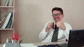 O gestor de escritório do homem com barba e vidros, café bebendo, mostra o polegar acima filme
