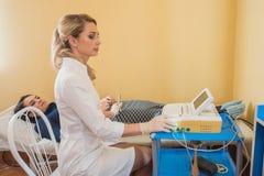 O ginecologista bonito faz o cardiotocography do feto Um doutor novo examina a para patien checkup foto de stock royalty free