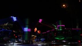 O giro colorido roda dentro o parque de diversões na noite vídeos de arquivo