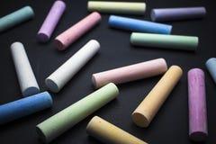 O giz das crianças coloridas em um fundo preto foto de stock