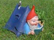 O gnomo do jardim encontra-se em sua casa de campo em um prado verde fotografia de stock