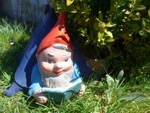O gnomo do jardim encontra-se em sua casa de campo em um prado verde Imagens de Stock Royalty Free
