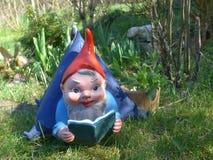 O gnomo do jardim encontra-se em sua casa de campo em um prado verde Fotografia de Stock Royalty Free