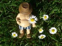 O gnomo do jardim encontra-se em um prado verde Imagem de Stock