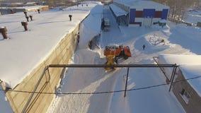 O graduador da vista aérea carrega a neve com a cubeta em Tipper Truck vermelha vídeos de arquivo