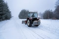 O graduador vermelho do snowblower cancela a estrada coberto de neve da estância de esqui fotografia de stock