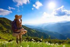 O gramado com os narcisos amarelos brancos nas montanhas altas ajardina A menina em meias dos overknees, vestido romântico Imagem de Stock Royalty Free
