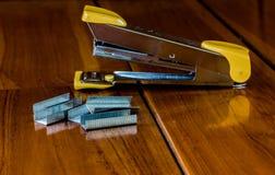 O grampeador está na madeira fotografia de stock