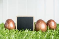O grampo vazio do quadro-negro e o ouro cor-de-rosa do coelho colorem ovos da páscoa sobre Foto de Stock