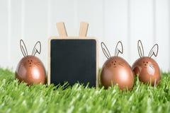 O grampo vazio do quadro-negro e o ouro cor-de-rosa do coelho colorem ovos da páscoa sobre Fotografia de Stock Royalty Free