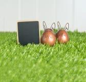 O grampo vazio do quadro-negro e o ouro cor-de-rosa colorem ovos da páscoa em g verde Foto de Stock