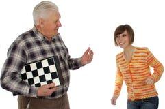 O Grandad chamou a neta para jogar uma xadrez Fotografia de Stock