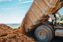 O grande caminhão descarrega a argila e a pedra esmagada imagem de stock