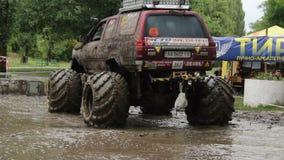 O grande carro de bigfoot completamente na sujeira gerencie ao redor a poça de lama filme