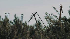 O grande frete do metal cranes sobre atrás de agitar arbustos vídeos de arquivo