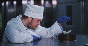 O grande homem do padeiro pôs a cereja para trás sobre o bolo com suas mãos grandes que vestem luvas azuis e olha fixamente no vídeos de arquivo