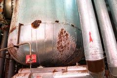 O grande permutador de calor do tanque na isolação isolada pela corrosão da oxidação com furos é idoso em uma refinaria de petról fotos de stock royalty free