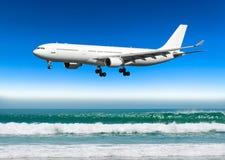O grande plano aproxima a aterrissagem no ponto baixo do aeroporto sobre uma praia tropical imagem de stock royalty free