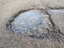 O grande poço encheu-se com água na coberta do asfalto, estrada quebrada, reflexão do ambiente na água, estradas ucranianas Imagens de Stock