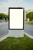 O grande quadro de avisos exterior está em uma interseção ocupada fotos de stock