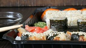 O grande sushi ajustou-se com uma variedade de rolos de sushi assim como maki, nigiri, gunkan em um fundo de madeira preto à moda video estoque