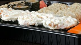 O grande sushi ajustou-se com uma variedade de rolos de sushi assim como maki, nigiri, gunkan em um fundo preto à moda Perto de vídeos de arquivo