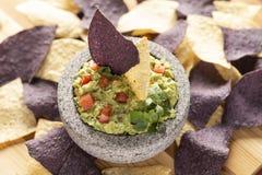 O granito Mulcajete encheu-se com o guacamole fresco cercado por microplaquetas de tortilha azuis e amarelas imagens de stock royalty free